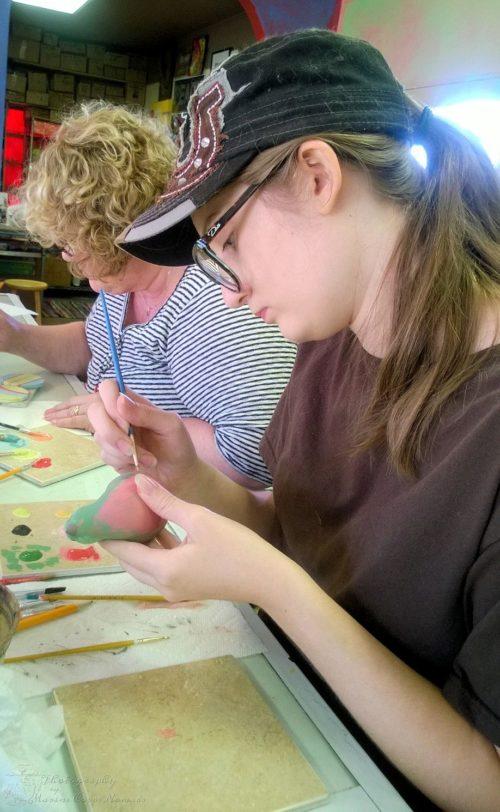 Munchkin painting her pottery bird