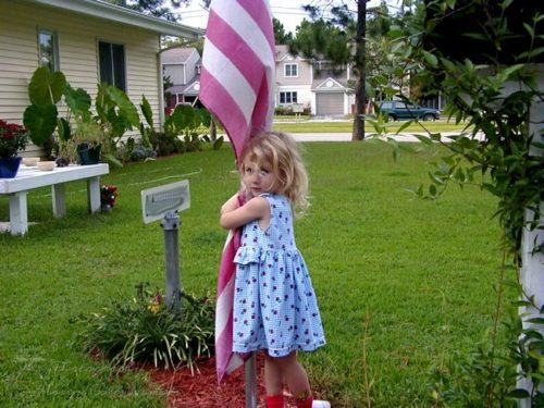Little Munchkin hugging our neighbor's flag.